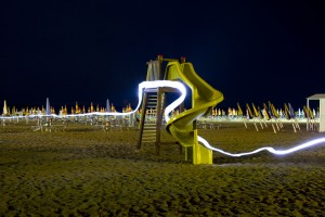 Beaches on the Italian Riviera buzz though the night under electric lights