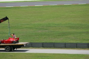 A car is recovered from the track at the Malasian Grand Prix