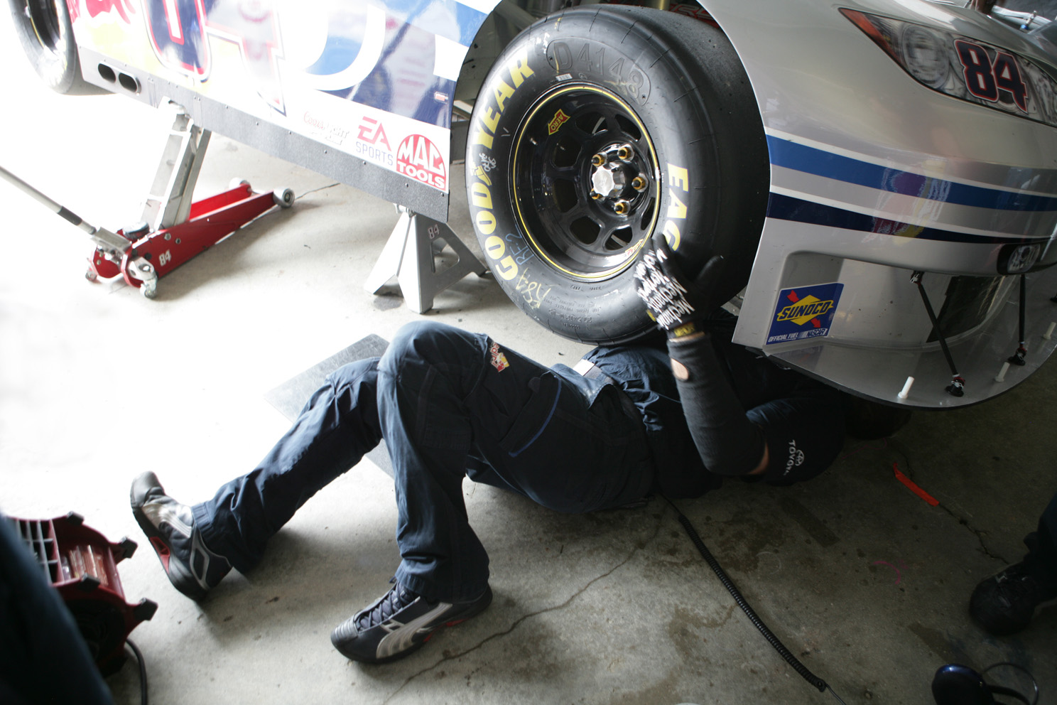 A Red Bull Team Member works on the car