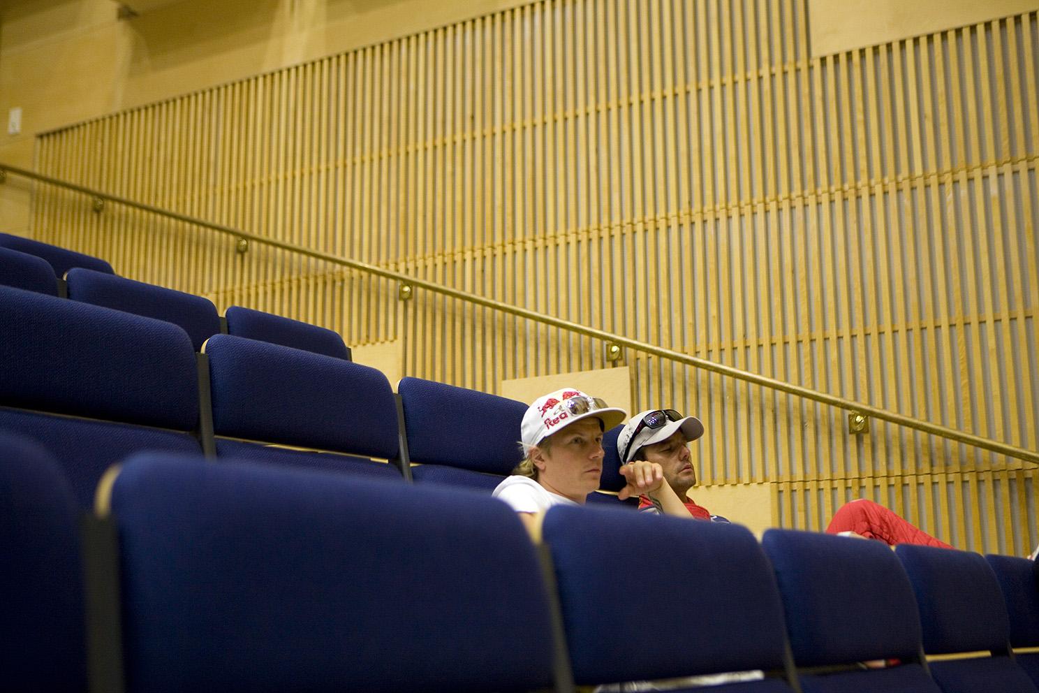 Kimi Raikkonen and Sebastien Loeb wait for the drivers meeting