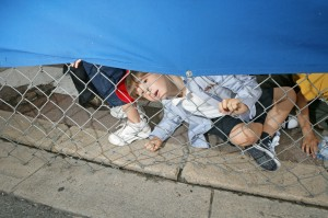 A young fan peeks under the fence to watch the action