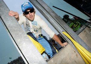 Fernando Alonso climbs over the pit wall
