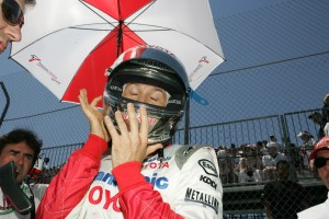 Jarno Trulli adjusts his head gear